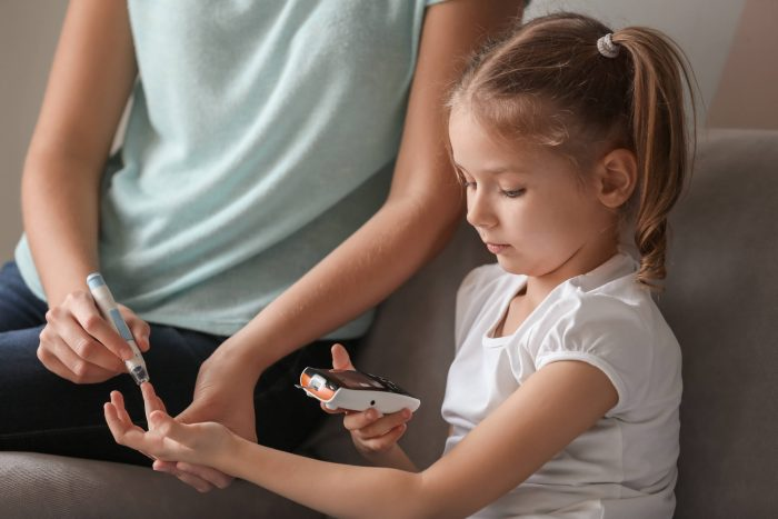Woman and her diabetic daughter with lancet pen and digital glucometer