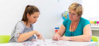 A mature woman supports a younger woman with learning disabilities. They both sit at a white table with shapes and paper in front of them. The younger woman points to one of the shapes on the table.