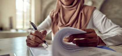 Muslim woman signing documents. Close up