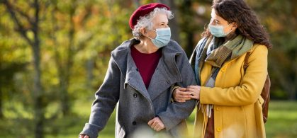 Two women walking arm in arm in the park with face masks on. One woman appears to be caring for the other who is older.